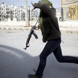 A Free Syrian Army fighter runs for cover during fighting against government...