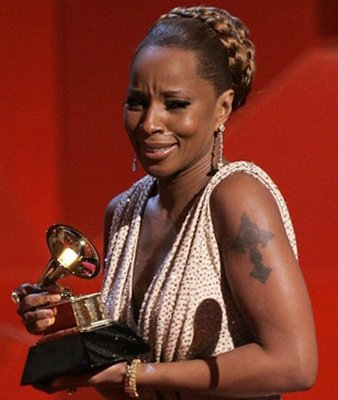 Mary J Blige displays a cross on her left arm as she accepts the award for
