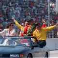 FILE - In this May 29, 1988 file photo, race car driver Rick Mears, second from right, team owner Roger Penske, right, and their wives, Kathy Penske, left, and Chris Mears, second from left, celebrate as they take a victory lap after the 72nd running of the Indianapolis 500 auto race at Indianapolis Motor Speedway in Indianapolis, Ind. (AP Photo/Mark A. Duncan, File)