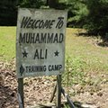 FILE - In this June 6, 2016, file photo, a sign is displayed outside Muhammad Ali's training camp in Deer Lake, Pa. The son of NFL Hall of Fame coach John Madden is buying Muhammad Ali's former training camp in Pennsylvania. The camp's longtime owner, martial arts instructor George Dillman, tells The Associated Press he has sold the rustic hilltop camp in Deer Lake to Mike Madden. He says the deal is closing Thursday, July 31, 2016. (AP Photo/Michael Rubinkam, File)
