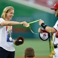 Olympic gold medal swimmer Katie Ledecky, left, hands her medals to Washington Nationals' Bryce Harper, right, to hold before she threw out the ceremonial first pitch before a baseball game between the Baltimore Orioles and the Washington Nationals, Wednesday, Aug. 24, 2016, in Washington. (AP Photo/Nick Wass)