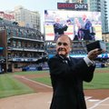 Dick Enberg, a San Diego Padres broadcaster, holds up a microphone trophy presented to him for his retirement, prior to the Padres' final baseball home game of the season, against the Los Angeles Dodgers on Thursday, Sept. 29, 2016, in San Diego. (AP Photo/Lenny Ignelzi)
