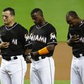 Miami Marlins third baseman Martin Prado, from left, shortstop Adeiny Hechavarria and left fielder Marcell Ozuna stand during a pre-game ceremony honoring pitcher Jose Fernandez before a baseball game against the New York Mets, Monday, Sept. 26, 2016, in Miami. Fernandez died in a boating accident Sunday. (AP Photo/Lynne Sladky)