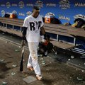 Miami Marlins' Dee Gordon wears a T-shirt reading RIP in honor of Marlins pitcher Jose Fernandez as he walks through the dugout after a baseball game against the New York Mets, Monday, Sept. 26, 2016, in Miami. Fernandez was killed in a boating accident early Sunday. The Marlins defeated the Mets 7-3. (AP Photo/Lynne Sladky)