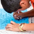 Luis Ruiz, 14, signs a remembrance shirt at a makeshift memorial in honor of Jose Fernandez sits outside Marlins Park, Sunday, Sept. 25, 2016. Jose Fernandez, the ace right-hander for the Miami Marlins who escaped Cuba to become one of baseball's brightest stars, was killed in a boating accident early Sunday morning. Fernandez was 24. (AP Photo/Gaston De Cardenas)