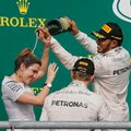 Mercedes driver Lewis Hamilton, upper right, of Britain, and Mercedes driver Nico Rosberg, lower right, of Germany, celebrate with a team member after Hamilton won the Formula One U.S. Grand Prix auto race at the Circuit of the Americas, Sunday, Oct. 23, 2016, in Austin, Texas. (AP Photo/Tony Gutierrez)