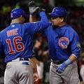 Chicago Cubs' Kyle Schwarber is congratulated by first base coach Brandon Hyde after hitting an RBI single during the fifth inning of Game 2 of the Major League Baseball World Series against the Cleveland Indians Wednesday, Oct. 26, 2016, in Cleveland. (AP Photo/David J. Phillip)