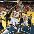 Virginia guard Devon Hall (0) takes a shot as West Virginia forward Sagaba Konate (50) defends during the first half of an NCAA college basketball game in Charlottesville, Va., Saturday, Dec. 3, 2016. West Virginia won the game 66-57.