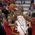 Texas guard Kendal Yancy, center, drives against Alabama guard Nick King, left, and forward Jimmie Taylor, right, during the first half of an NCAA college basketball game, Friday, Dec. 2, 2016, in Austin, Texas.